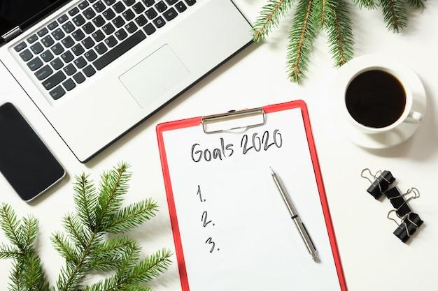 Biurowe miejsce pracy z laptopem i lista celów 2020 Premium Zdjęcia