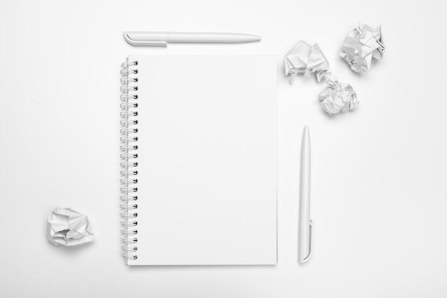 Biurowe miejsce pracy z pustym notatnikiem, zmięty papier Premium Zdjęcia