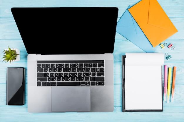 Biurowe niebieskie biurko z laptopem i materiałami szkolnymi Darmowe Zdjęcia