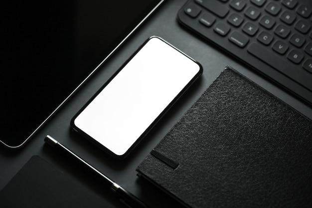 Biurowe z pustego ekranu inteligentny telefon na ciemnym tle. Premium Zdjęcia
