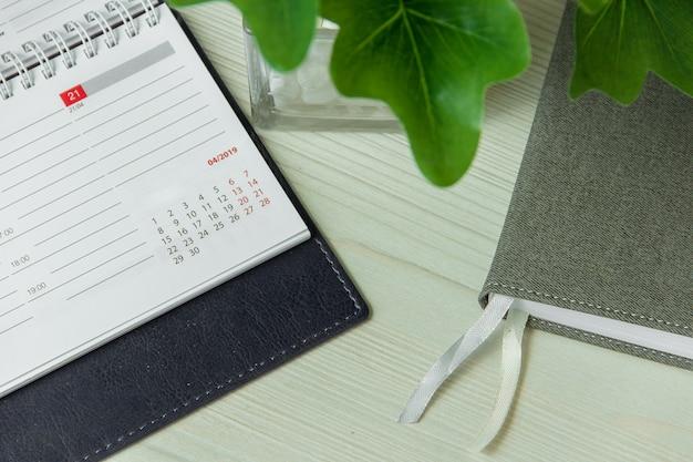 Biurowy miejsce pracy z notatnikiem i garnek rośliny zakończeniem up. Premium Zdjęcia