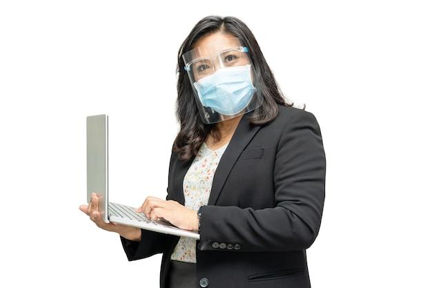 Biznes Azjatycka Dama Noszenie Osłony Twarzy I Maski Na Twarz Trzymając Laptopa. Premium Zdjęcia
