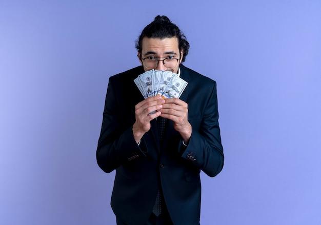 Biznes Człowiek W Czarnym Garniturze I Okularach Trzyma Gotówkę Patrząc Zaskoczony I Zdumiony Stojąc Nad Niebieską ścianą Darmowe Zdjęcia