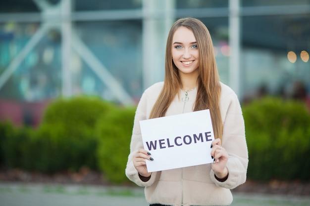 Biznes kobiet z plakatem z wiadomością powitalną Premium Zdjęcia