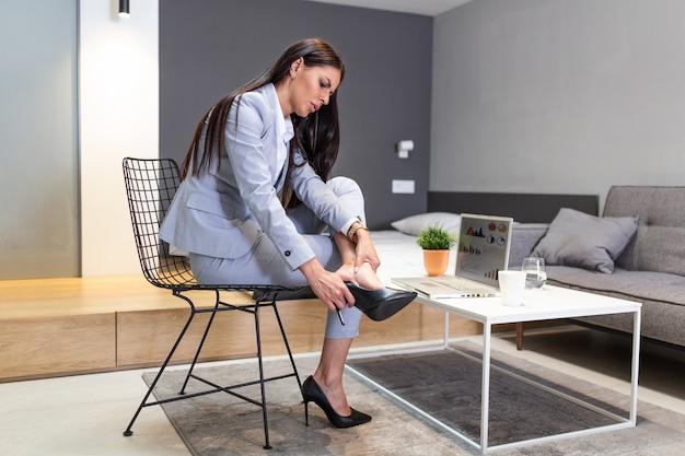 Biznes Kobieta Siedzi Na Krześle, Trzymać Nogi Ma Objaw Bólu żylaków Od Wysokich Obcasów. Premium Zdjęcia