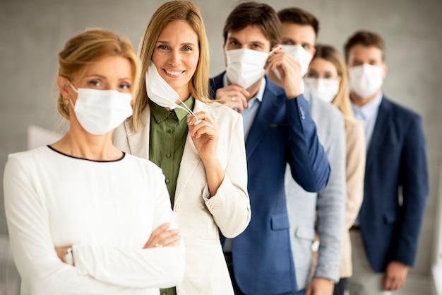 Biznes Kobieta Zdejmując Ochronną Maskę Na Twarz I Patrząc W Kamerę Z Członkami Zespołu Premium Zdjęcia