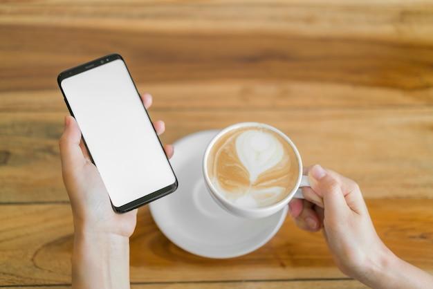 Biznes strony z telefonu komórkowego i kawy latte sztuki. Darmowe Zdjęcia