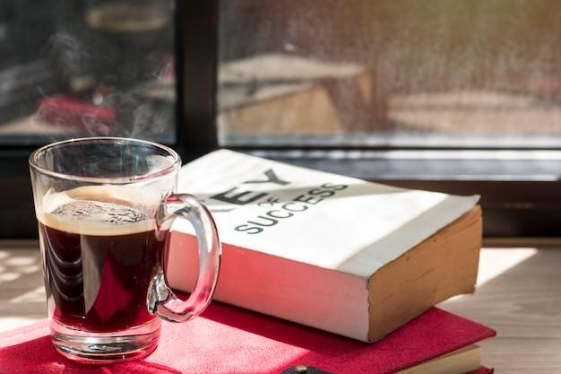 Biznes sukces książka i czarna kawa na drewnianym pobliskim okno w lekkim ranku Premium Zdjęcia