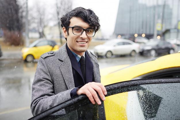 Biznesmen biorąc taksówkę w deszczu Darmowe Zdjęcia