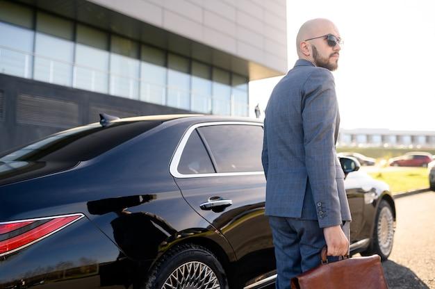 Biznesmen Chodzi Na Tle Budynku I Samochodu Premium Zdjęcia