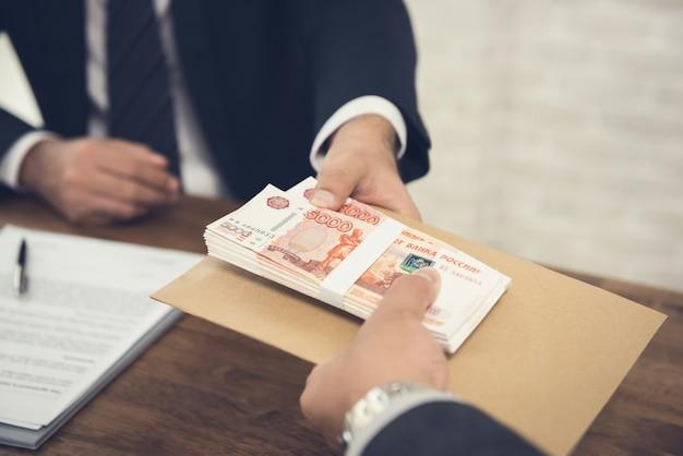 Biznesmen daje rubelowi rosyjskiemu swojemu partnerowi Premium Zdjęcia