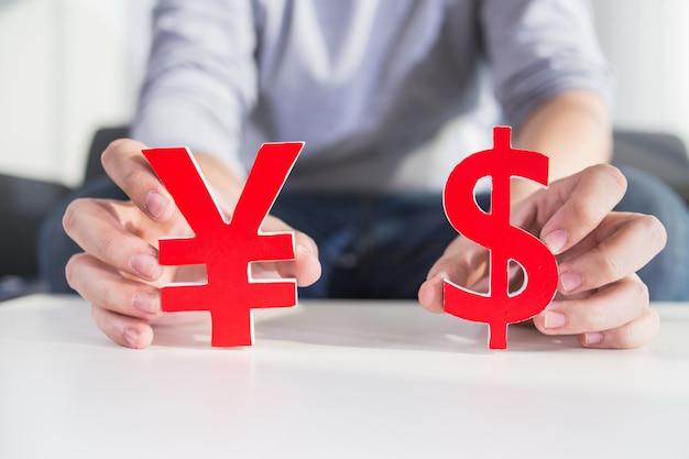 Biznesmen gospodarstwa znak dolara i znak cny Darmowe Zdjęcia