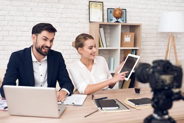 Biznesmen i bizneswoman w bluzce pokazuje na pastylce Premium Zdjęcia