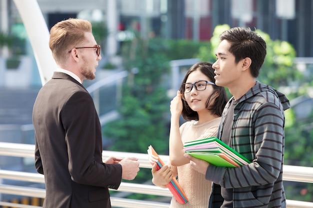 Biznesmen I Studenci Collegu Dyskutuje Edukację Premium Zdjęcia