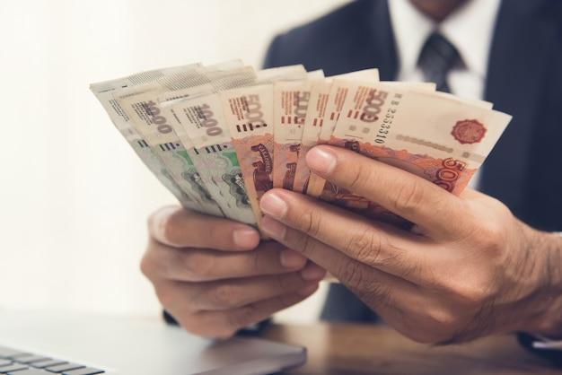 Biznesmen liczenia pieniędzy, waluty rubel rosyjski, przy swoim biurku Premium Zdjęcia