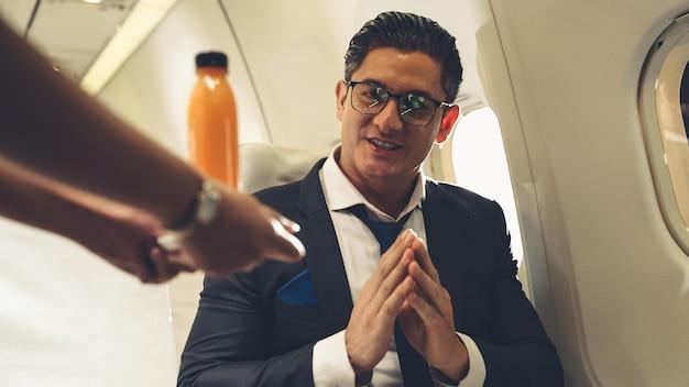 Biznesmen ma sok pomarańczowy podawany przez stewardessę w samolocie Premium Zdjęcia