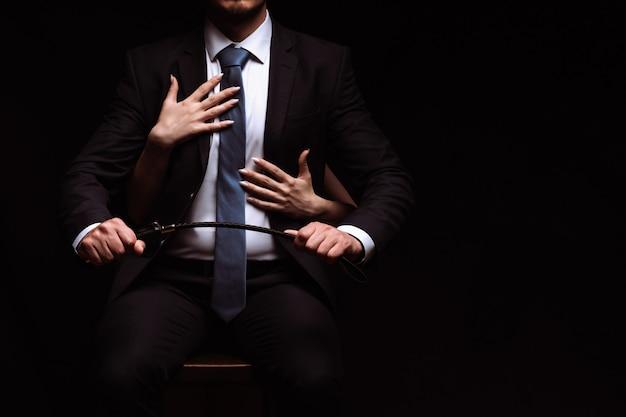 Biznesmen Mężczyzna W Garniturze Ze Skórzanym Biczem Siedzi Na Krześle, A Uległa Osoba Obejmuje Go Ramionami Premium Zdjęcia