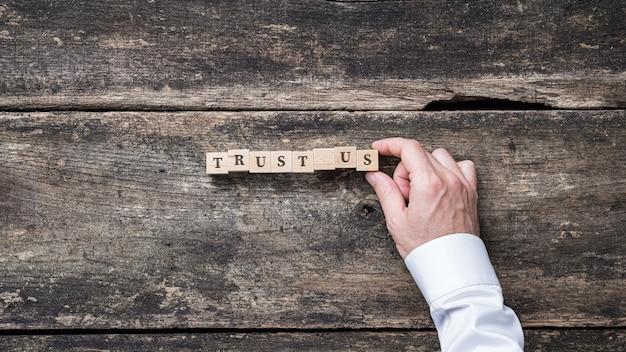 Biznesmen Montujący Napis Trust Us Zapisany Na Drewnianych Klockach. Premium Zdjęcia