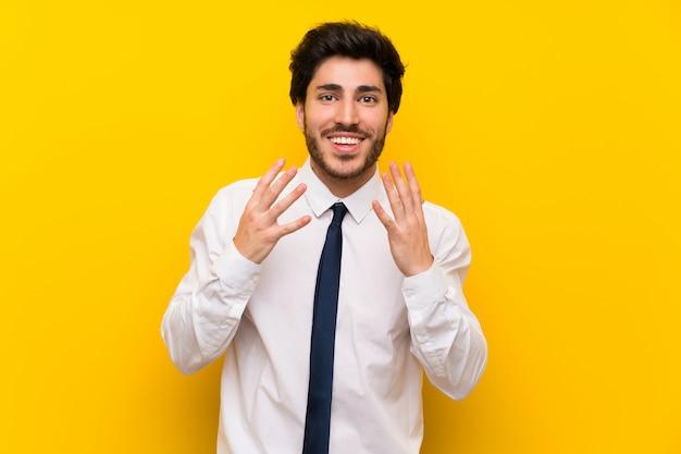 Biznesmen na odosobnionej kolor żółty ścianie z niespodzianka wyrazem twarzy Premium Zdjęcia