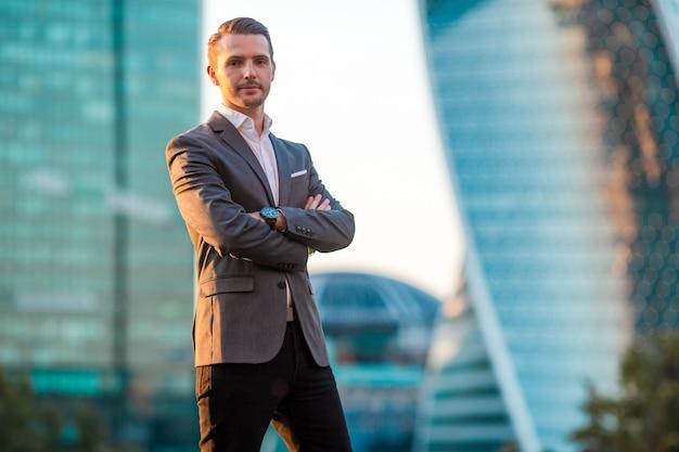 Biznesmen Patrzeje Na Kopii Przestrzeni Podczas Gdy Stojący Przeciw Szklanemu Drapaczowi Chmur Premium Zdjęcia