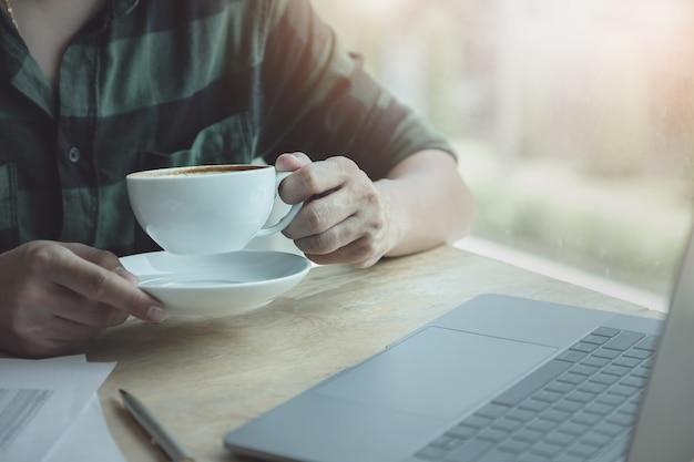 Biznesmen pije kawę podczas pracy z laptopem Premium Zdjęcia
