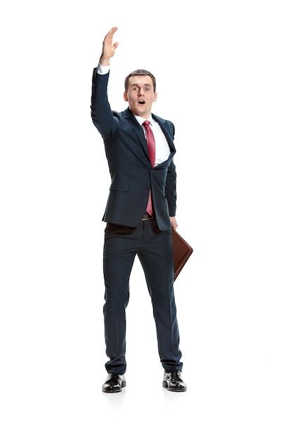 Biznesmen, Podnosząc Rękę Na Tle Białego Studia. Poważny Młody Człowiek W Garniturze. Biznes, Koncepcja Kariery. Darmowe Zdjęcia