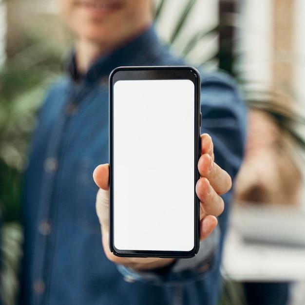 Biznesmen Pokazuje Telefon Z Pustym Ekranem Darmowe Zdjęcia