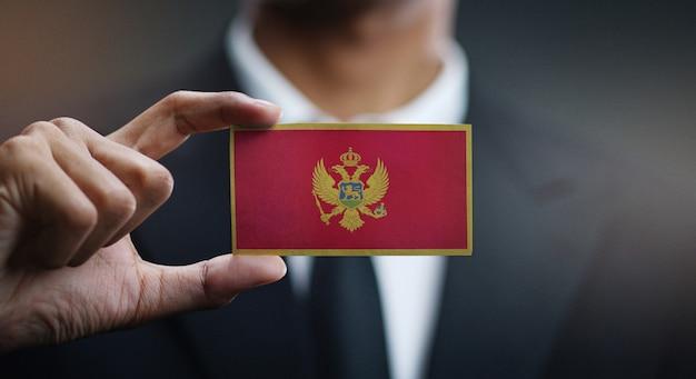 Biznesmen Posiadający Kartę Flagi Czarnogóry Premium Zdjęcia