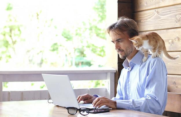 Biznesmen Pracuje Na Laptopie Na Otwartym Tarasie, Kotek Siedzi Na Jego Ramieniu Premium Zdjęcia