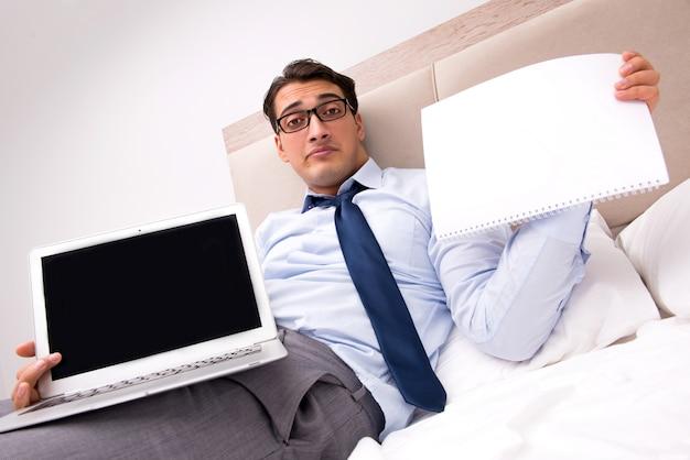 Biznesmen pracuje w łóżku w domu Premium Zdjęcia