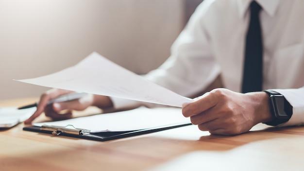 Biznesmen pracuje w swoim biurze z dokumentami i sprawdzić dokładność informacji. Premium Zdjęcia