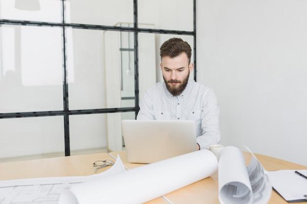 Biznesmen pracuje z laptopem w biurze Darmowe Zdjęcia