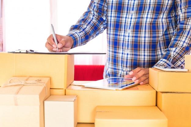 Biznesmen pracuje z telefonem komórkowym i pakuje brown pakuneczek boksuje w domu biuro. sprzedawca rąk przygotowuje produkt gotowy do dostarczenia do klienta. sprzedaż online, e-commerce rozpocznij koncepcję wysyłki. Premium Zdjęcia