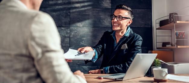 Biznesmen przechodzi kontrakt do swojego klienta Premium Zdjęcia