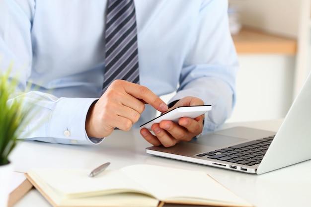 Biznesmen Ręce Wpisując Coś Na Inteligentny Telefon Siedzi W Jego Biurze. Zamknąć Widok Premium Zdjęcia