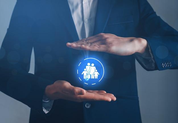 Biznesmen Ręce Z Ochronnym Gestem I Ikoną Rodzina. Pojęcie Ubezpieczenia Rodzinnego. Premium Zdjęcia