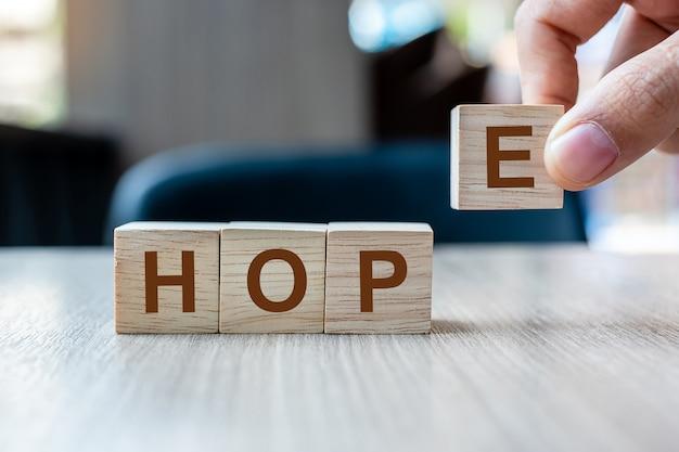 Biznesmen ręka trzyma drewnianego sześcianu blok z nadziei biznesowym słowem na stołowym tle. Premium Zdjęcia