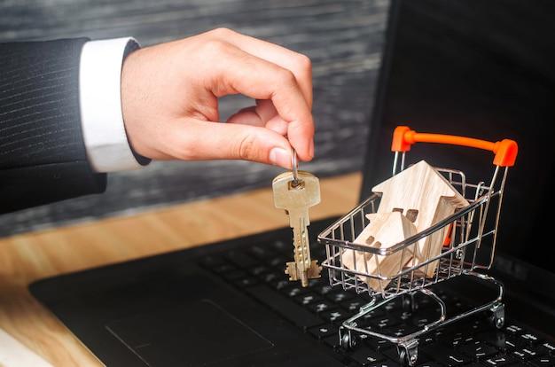 Biznesmen ręka trzyma klucze blisko taczki z domami. Premium Zdjęcia