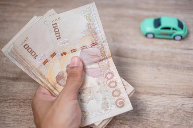 Biznesmen ręka trzyma tajlandzkiego bahta banknotu stertę z samochodem. Premium Zdjęcia