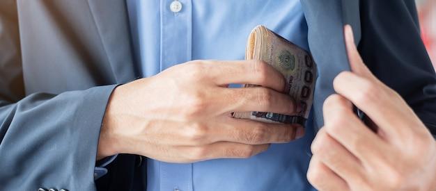 Biznesmen ręka trzyma tajlandzkiego bahta banknotu stertę. Premium Zdjęcia