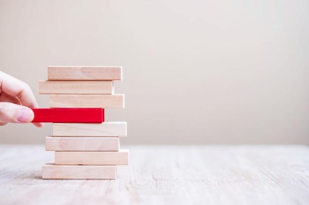 Biznesmen Ręka Umieszcza Czerwonego Drewnianego Blok Na Wierza Lub Ciągnie. Planowanie Biznesowe, Zarządzanie Ryzykiem, Rozwiązania, Rozwiązania I Strategie Premium Zdjęcia