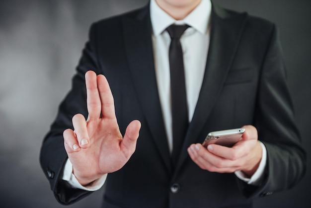 Biznesmen ręka wskazuje na pustej przestrzeni na czarnym tle Premium Zdjęcia