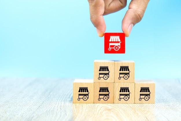 Biznesmen Ręka Wybiera Czerwonego Koloru Drewnianego Zabawkarskiego Blog Brogującego Z Franczyzy Ikon Marketingowym Sklepem. Premium Zdjęcia