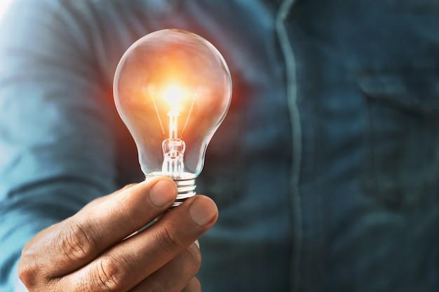 Biznesmen Ręki Mienia Lightbulb Z światłem Słonecznym. Premium Zdjęcia