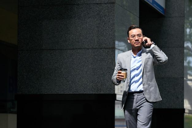 Biznesmen robi rozmowie telefonicza w drodze outdoors Darmowe Zdjęcia
