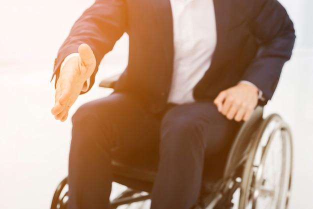 Biznesmen siedzi na wózku inwalidzkim wyciągając rękę, aby wstrząsnąć Darmowe Zdjęcia