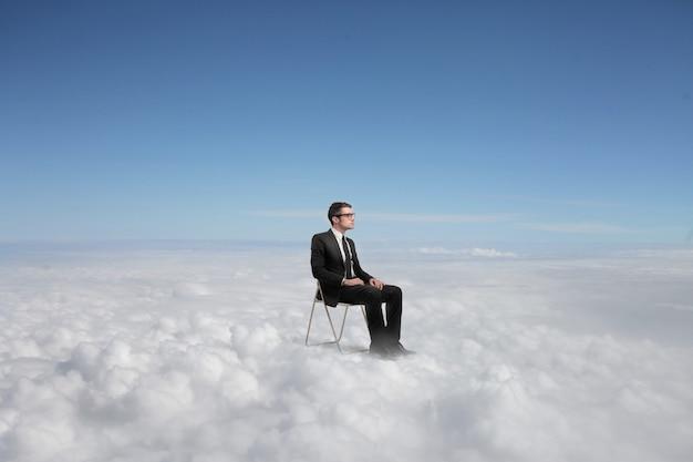 Biznesmen siedzi ponad chmurami Premium Zdjęcia
