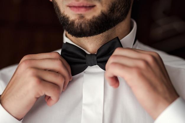 Biznesmen, Stawiając Na Muszkę, Ubrania Motyla Człowieka, Przygotowuje Się Rano Przed Ceremonią ślubną. Moda Męska Premium Zdjęcia