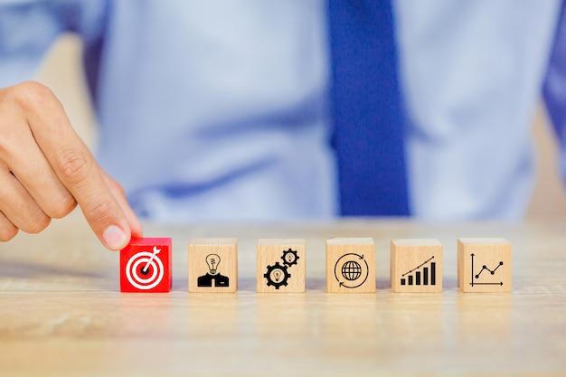 Biznesmen strony wprowadzenie blok sześcian drewna na górze z koncepcją sukcesu cel. Premium Zdjęcia