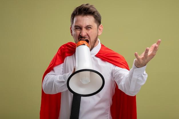 Biznesmen Superbohatera W Czerwonej Pelerynie Krzycząc Do Megafonu Z Agresywnym Wyrazem Ręki Stojącej Na Zielonym Tle Darmowe Zdjęcia